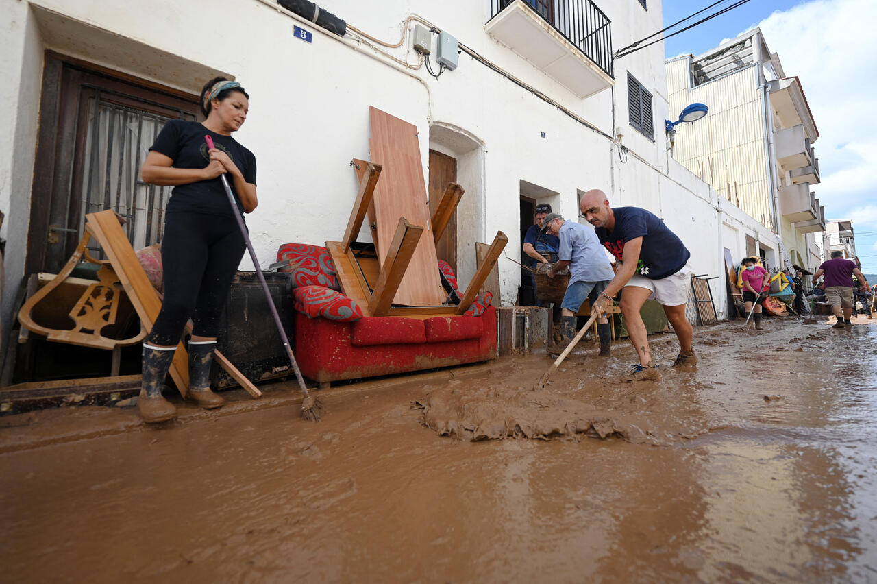 Los residentes intentan quitar el barro de las calles en Alcanar, el 2 de septiembre de 2021, un día después de que las inundaciones repentinas afectaran el área. Horas de fuertes lluvias provocaron inundaciones en el este de España ayer con algunas áreas costeras abrumadas por inundaciones repentinas que arrasaron automóviles y árboles. Una de las zonas más afectadas fue Alcanar, una ciudad a 200 kilómetros (160 millas) al sur de Barcelona, donde inmensos torrentes de agua en rápido movimiento surgieron por las calles, arrasando con todo a su paso.