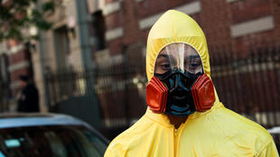 A young man, dressed in a biohazard costume, stands on the corner of 546 West 147th Street on October 25, 2014 in New York City, where a doctor was recently diagnosed with Ebola after returning from Guinea