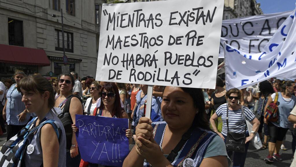 """Archivo: una maestra sostiene una pancarta que dice: """"Mientras haya profesores de pie, no habrá personas arrodilladas"""" durante una huelga nacional de 48 horas que exigía aumentos salariales, en Buenos Aires el 6 de marzo de 2017."""