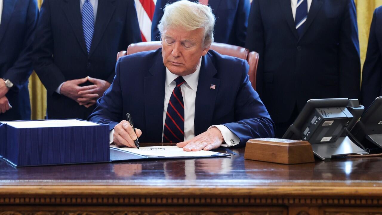 El presidente de Estados Unidos, Donald Trump, firma en su despacho el paquete de ayuda para combatir el coronavirus. Washington D. C., Estados Unidos, 27 de marzo de 2020.