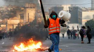 Un manifestante pasa junto a objetos en llamas en una carretera durante una protesta contra el Gobierno de Sebastián Piñera. Valparaíso, Chile, el 19 de octubre de 2019.