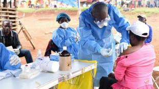 Un funcionario del Ministerio de Sanidad del RDC vacuna contra el Ébola a una mujer que estuvo en contacto con una paciente infectada con el virus en la villa de Mangina en la provincia de Kivu del Norte en el noreste de la República Democrática del Congo. Foto de archivo. 18 de diciembre. 2018