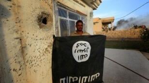 """جندي عراقي يحمل علم تنظيم """"الدولة الإسلامية"""" بالمقلوب في قرية جارف قرب الموصل"""