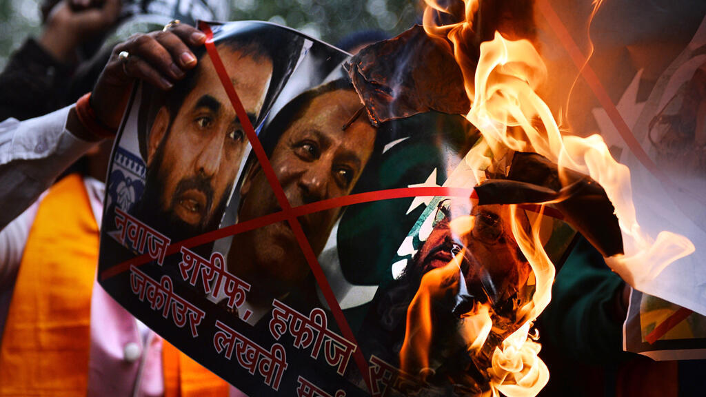 Indian protesters burn a poster bearing images of alleged planners of the 2008 Mumbai attacks Hafiz Muhammad Saeed and Zaki-ur-Rehman Lakhvi, as well as Pakistani Prime Minister Nawaz Sharif, in New Delhi on December 19, 2014