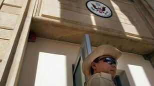 (FILES) -- File picture dated June 29, 2004 shows a private security guard standing at the front entrance of the new US embassy building in in Baghdad's Green Zone