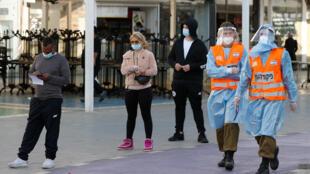 جنود من قيادة الجبهة الداخلية الإسرائيلية يسيرون في شوارع منتجع نتانيا المركزي لإرشاد السكان على أماكن خيام اختبار فيروس كورونا في 7 فبراير/ شباط 2021.