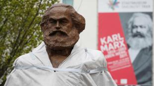 Trabajadores alemanes montaron una escultura de bronce de Karl Marx en su ciudad natal, Tréveris, Alemania, el 13 de abril de 2018.