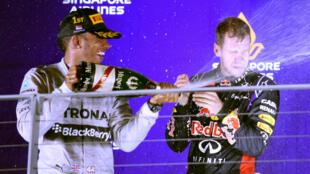 Nouveau leader du championnat du monde, Lewis Hamilton célèbre sa victoire avec le champion en titre Sebastian Vettel.