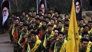 مقاتلون من حزب الله في مسيرة بلبنان رافعين رايات حزبية وصور لحسن نصرالله والخميني وخامنئي