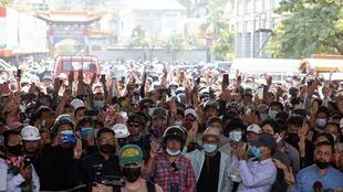People hold up the three finger salute during the funeral procession for protester Kyal Sin, in Mandalay on March 4, 2021, a day after she was shot in the head during a protest.