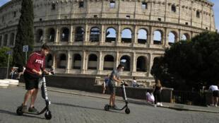 اشخاص ايطاليون يركبون دراجات كهربائية أمام كولوسيوم في روما في 28 أيار/مايو 2020.