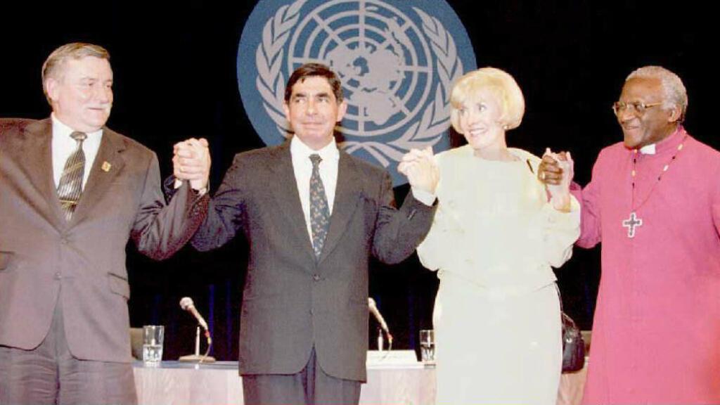 Los ganadores del Premio Nobel de la paz: Lech Walesa,  Oscar Arias Sánchez, expresidente de Costa Rica, Betty Williams de Irlanda del Norte y el Arzobispo anglicano Desmond Tutu, se toma de la mano el 25 de junio de 1995, en un foro en San Francisco, EE. UU.