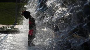 Una niña se enfría en una fuente de agua durante la ola de calor en Washington, D. C. Sábado 20 de julio de 2019.