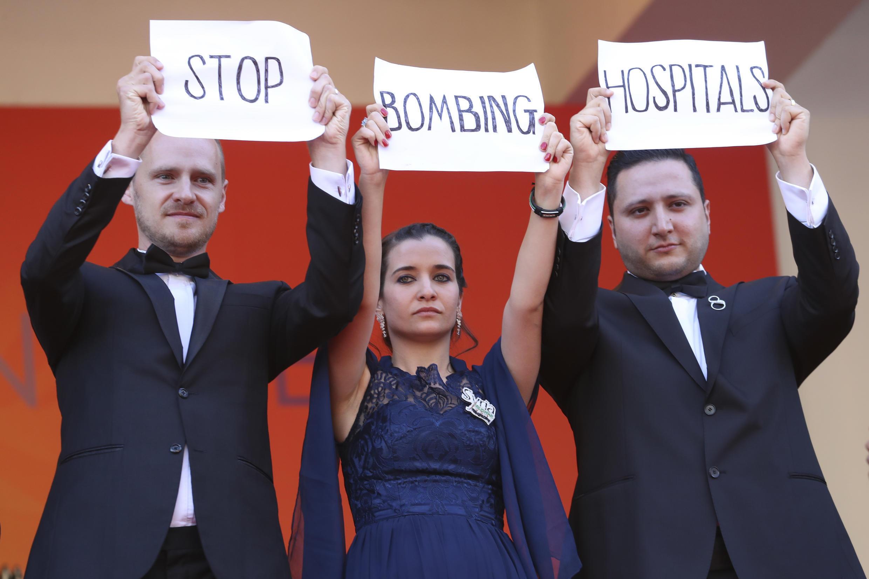"""Los miembros del equipo de la película For Sama, los directores Edward Watts y Waad Al Kateab muestran pancartas que dicen """"Paran de bombardear hospitales"""" cuando llegan para la proyección de la película """"Les Miserables"""" en la 72ª edición del Festival en Cannes, el 15 de mayo de 2019."""