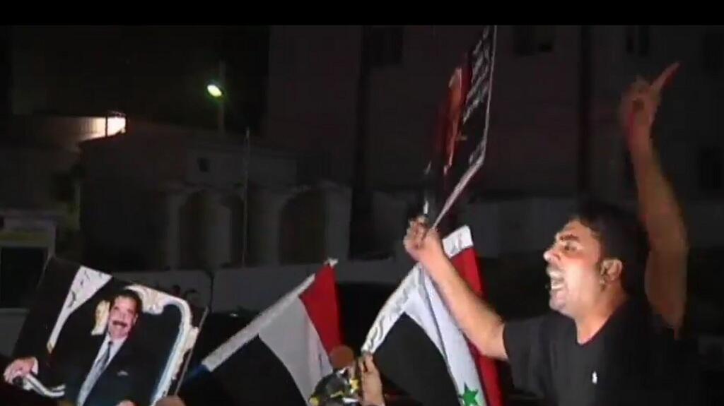 صورة ملتقطة عن الفيديو لمؤيدي نظام صدام لدى استقبال جثمان طارق عزيز في الأردن