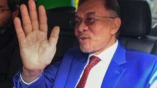 Malaysian opposition leader Anwar Ibrahim waves after meeting the king. Anwar has sought to become prime mnister for more than two decades
