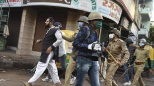 الشرطة في غوجارات تقتاد شخصا كان يرشقها بالحجارة في منطقة شهبور، خلال تدابير الإغلاق المفروضة للحد من تفشي فيروس كورونا، في 8 أيار/مايو 2020