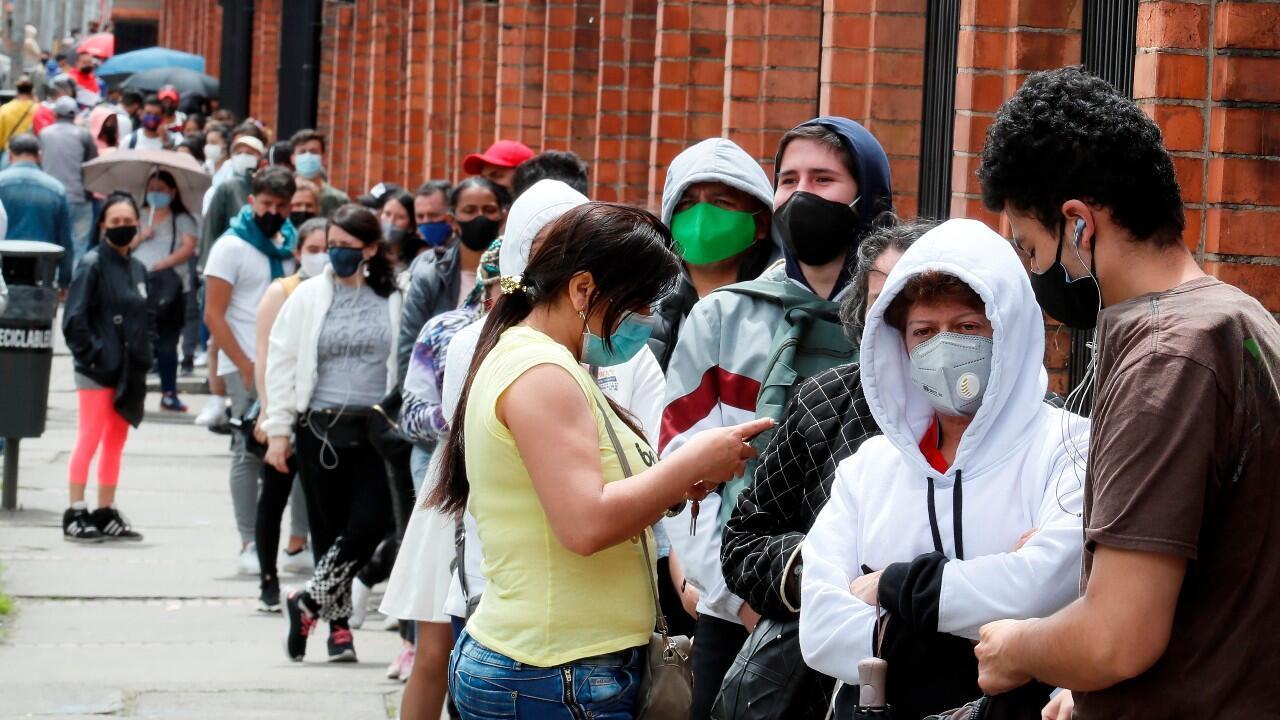 Compradores hacen fila para ingresar a un almacén este viernes en Bogotá, Colombia.  Miles de personas desafiaron el contagio del COVID-19 haciendo largas filas sin distanciamiento y aglomerados en almacenes durante el primer Día sin IVA, impuesto sobre el valor agregado, decretado por el Gobierno nacional para reactivar el comercio durante la pandemia.