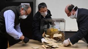 Des scrutateurs effectuent le dépouillement des bulletins de vote lors du premier tour des élections municipales dans un bureau de vote à Strasbourg, dans l'est de la France, le 15 mars 2020.