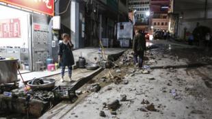 امرأة تقف خارج مطعم بعد الزلزال الذي ضرب منطقة كاوجي في الصين في 19 أيار/مايو 2020