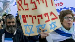 """""""On n'abandonne jamais ses soldats"""", peut-on lire sur la pancarte de la femme israélienne qui manifeste, mercredi 4 janvier à Tel Aviv, en soutien au soldat Elor Azaria."""