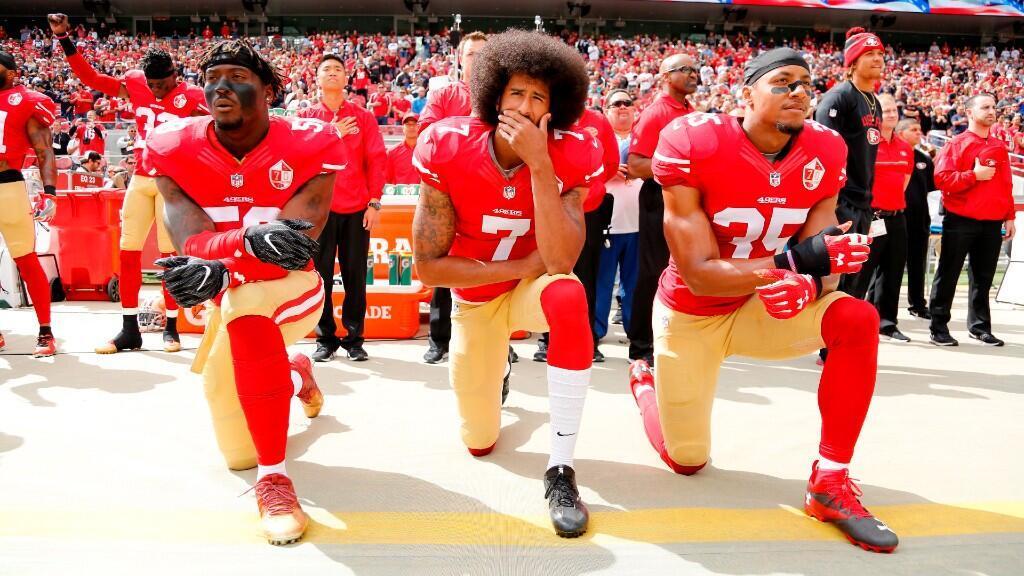 Colin Kaepernick (centro), se arrodilla junto con Eli Harold (izquierda) y Eric Reid (derecha) ante el himno nacional de Estados Unidos en un partido de la NFL en Santa Clara, el 2 de octubre de 2016.