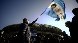 احد مشجعي نادي نابولي الإيطالي يرفع العلم الارجنتيني وفي وسطه صورة الاسطورة دييغو مارادونا أمام ملعب الفريق الجنوبي، في 26 تشرين الثاني/نوفمبر 2020