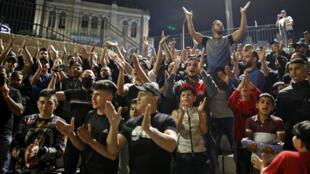متظاهرون فلسطينيون يهتفون فرحاً بعد تمكنهم من الوصول إلى باب العمود في البلدة القديمة بالقدس الشرقية في 25 نيسان/أبريل 2021.