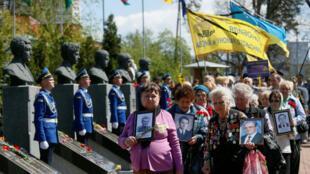 Varias mujeres portan retratos de sus familiares, que fueron víctimas del desastre nuclear de Chernóbil, durante una ceremonia conmemorativa en Kiev, Ucrania, el 26 de abril de 2018.