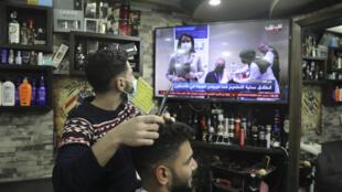 حلاق يطالع شاشة الأخبار عبر شاشة التلفاز في مدينة نابلس في الضفة الغربية المحتلة في الثاني من شباط/فبراير 2021 حيث أعلنت السلطة الفلسطينية بدء حملة التلقيح ضد فيروس كورونا