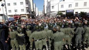 متظاهرون يهتفون أمام قوات الأمن المغربية خلال مسيرة تتحدى المنع الذي فرضته السلطات في مدينة الحسيمة المغربية، 20 تموز/يوليو، 2017