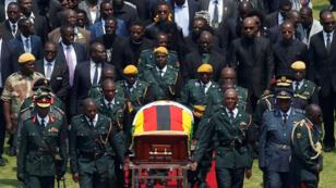 Oficiales trasladan el ataúd con el cuerpo del expresidente Robert Mugabe en el Estadio Nacional de Harare. 14 de septiembre de 2019.