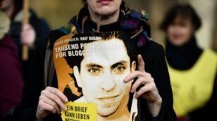 ناشطة من منظمة العفو الدولية تحمل صورة للمدون السعودي رائف بدوي خلال تظاهرة في برلين