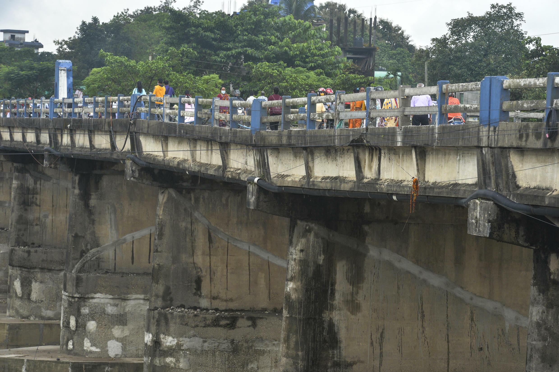 Varias personas cruzan el puente Balason, cerrado después de que uno de sus pilares resultara dañado por las fuertes lluvias, en la ciudad india de Siliguri el 21 de octubre de 2021