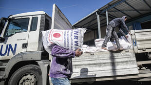 A man transports a sack of flour as people come to receive food aid from a United Nations Relief and Works Agency (UNRWA) centre in the Khan Yunis camp for Palestinian refugees in the Gaza Strip