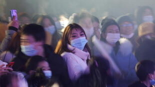 People wearing face masks attend a celebration event on New Year's Day, amid the coronavirus disease (COVID-19) outbreak, at a park in Wuhan, Hubei province, China January 1, 2021.