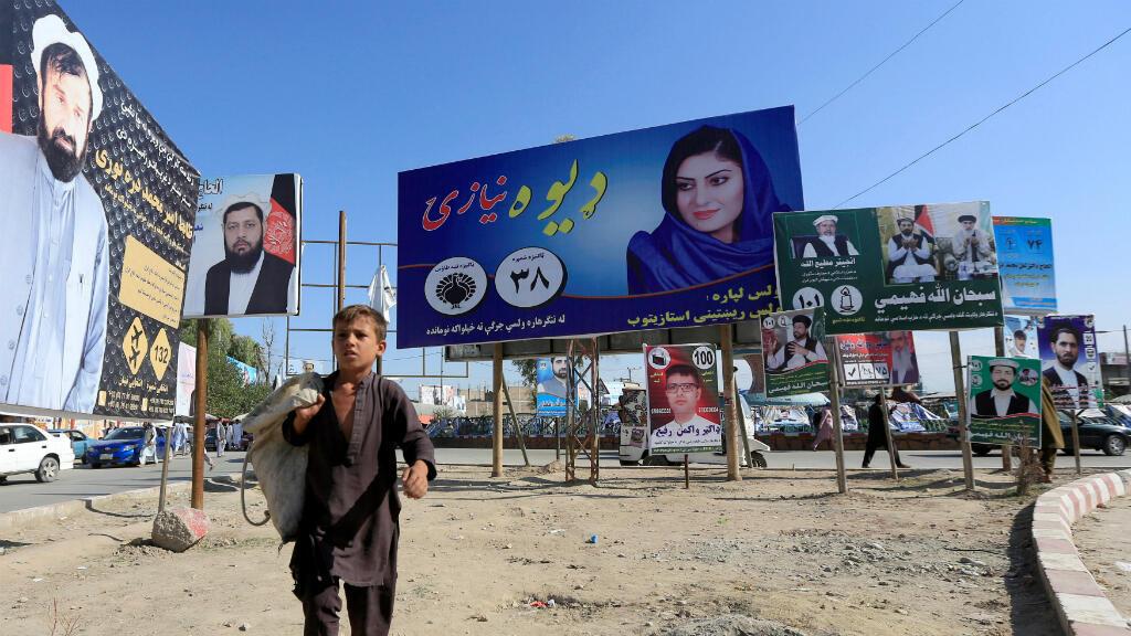 Hay 417 candidatas en esta campaña, más que en cualquier otro momento de la historia electoral de Afganistán. En la imagen, un niño camina frente a una serie de carteles de propaganda en Jalalabad, Afganistán, el 6 de octubre de 2018.