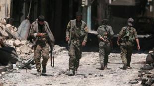 Combatientes de las Fuerzas Democráticas Sirias (FDS) caminan entre las ruinas en la ciudad de Manbij, el 10 de agosto de 2016.