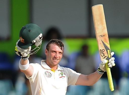 Australian batsman Phillip Hughes raises his bat and helmet in celebration in 2011.