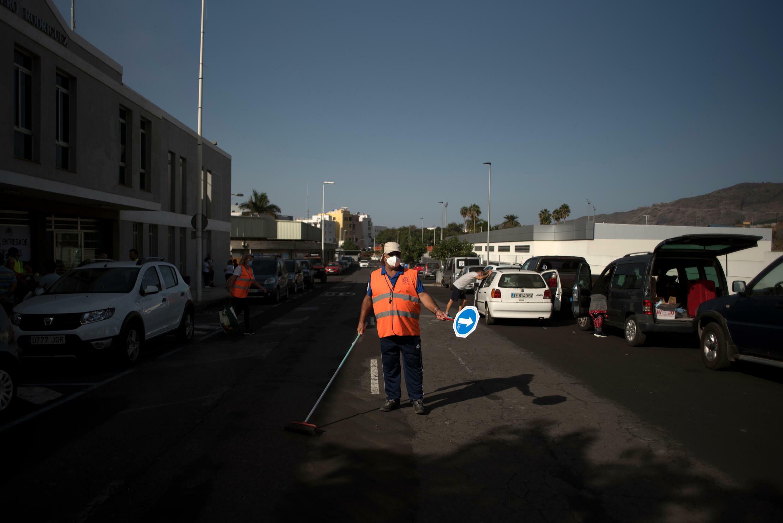 Unos trabajadores limpian una carretera cubierta de ceniza por la erupción del volcán Cumbre Vieja, en la isla canaria de La Palma, el 2 de octubre de 2021