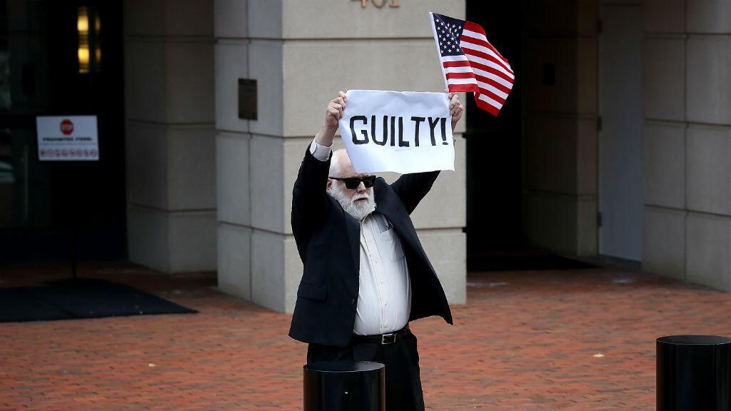 """Un manifestant esseulé tient une pancarte """"Coupable!"""" à Alexandria, lors du verdict du procès de Paul Manafort, mardi 21 août."""
