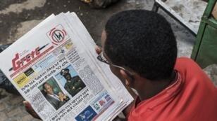 Un homme lisant les portaits d'Ambachew Mekonen (g), tué, et du général Sere Mekonen, dans le journal The reporter du 24 juin 2019.