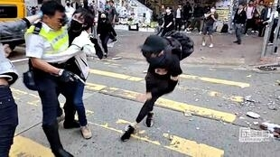 A still image from a social media video shows a protester try to prevent a police officer from aiming his gun at a protester in Sai Wan Ho, Hong Kong, China November 11, 2019.