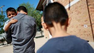 Epigmenio Centeno carga su hijo de tres años mientras su otro hijo de nueve, lo sigue, afuera del refugio House of the Migrant, en Ciudad Juárez, México, el 19 de junio de 2018.