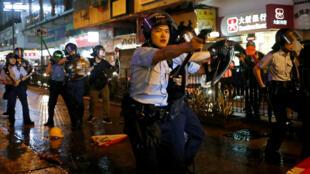 Oficiales de policía apuntan con sus armas a los manifestantes después de un enfrentamiento, en Tsuen Wan, Hong Kong, el 25 de agosto de 2019.