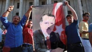 مواطنون أتراك يحملون صورة إردوغان أثناء تظاهرهم تنديدا بالانقلاب