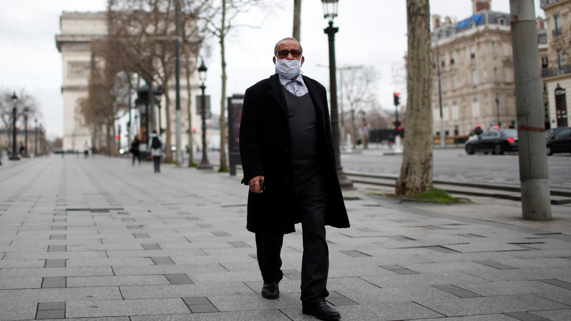 Un hombre con una máscara protectora camina por la avenida de los Campos Elíseos, cerca del Arco de Triunfo en París, mientras las tiendas y las escuelas permanecen cerradas y los trabajadores deben trabajar desde casa si es posible, parte de las últimas medidas gubernamentales francesas contra la enfermedad por el coronavirus.
