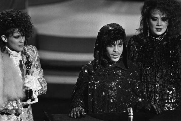 """Le chanteur américain Prince (au centre) reçoit l'Oscar de la meilleure partition originale, pour """"Purple Rain"""", lors de la 57e remise des Oscars à Hollywood, le 25 mars 1985."""