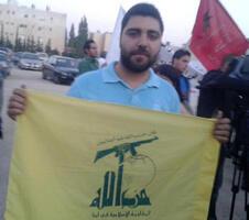 صورة نشرها على فيسبوك خلدون غرايبة لناشط شيوعي يحمل راية حزب الله في تظاهرة بالأردن تأييدا للحزب وللنظام السوري.