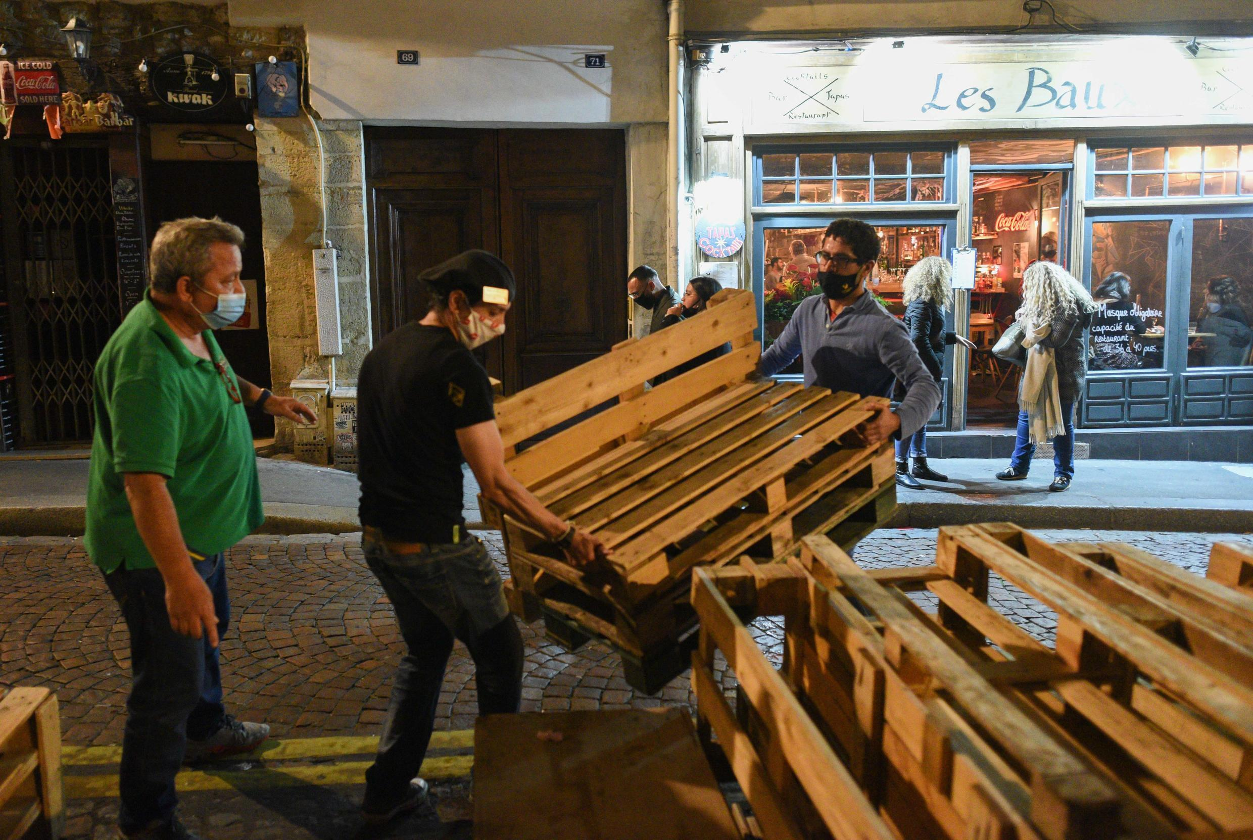 Michel Lironis (L) and his crew remove wooden pallets used for an open-air terrace before closing the restaurant.